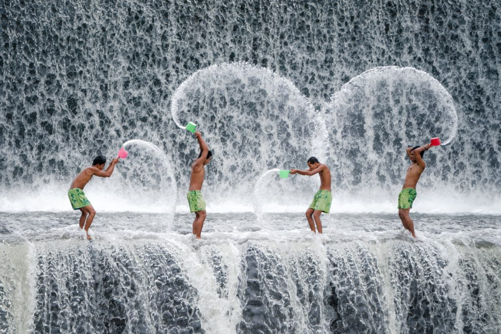 Men washing in waterfall