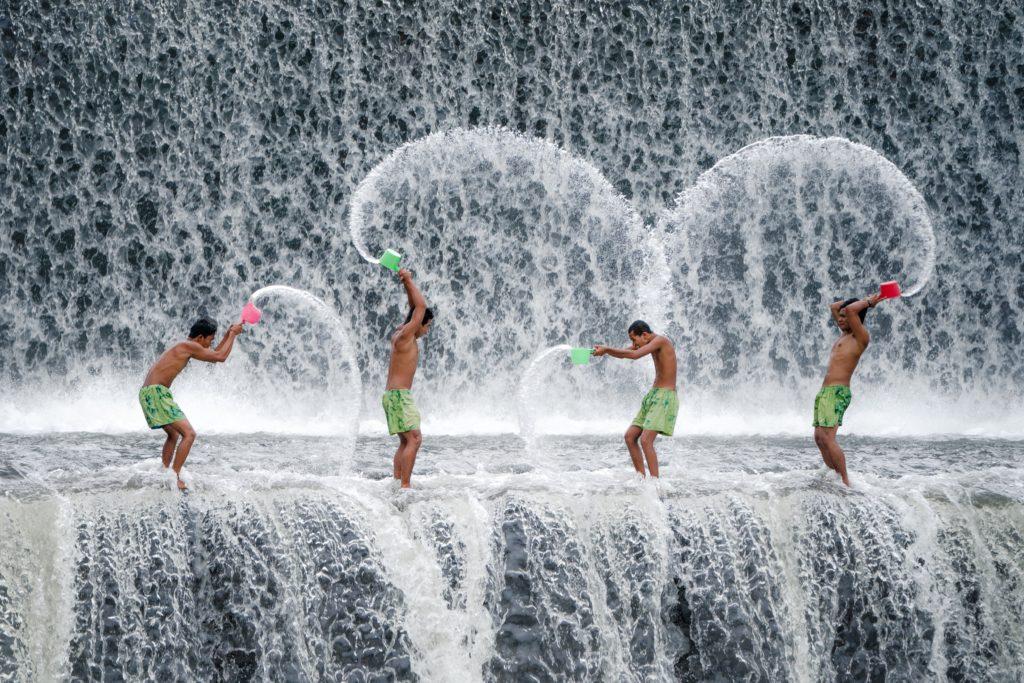 Men washing in waterfall