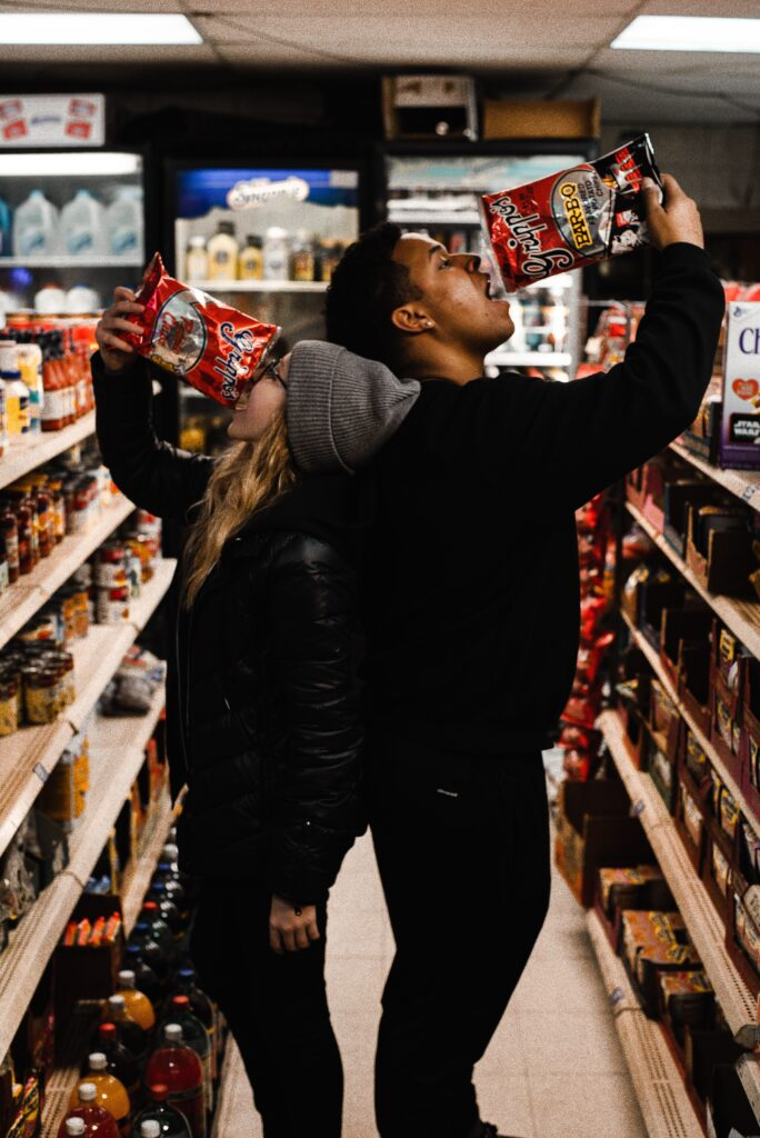 two people eating chips in store